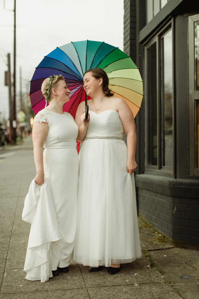 picture of two women holding rainbow umbrella