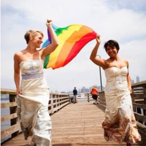 two brides on a dock with a rainbow flag